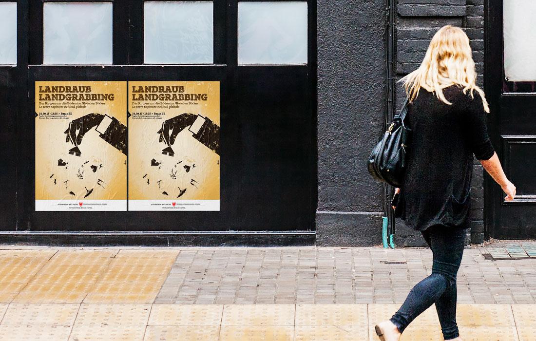 """Plakat """"Landraub, Land grabbing: Das Ringen um die Böden im Globalen Süden"""" im urbanen Umfeld. Ein ökosozialer Poster in Südtirol, Bozen. Grafik von der adpassion Werbeagentur, Waldemar Kerschbaumer."""