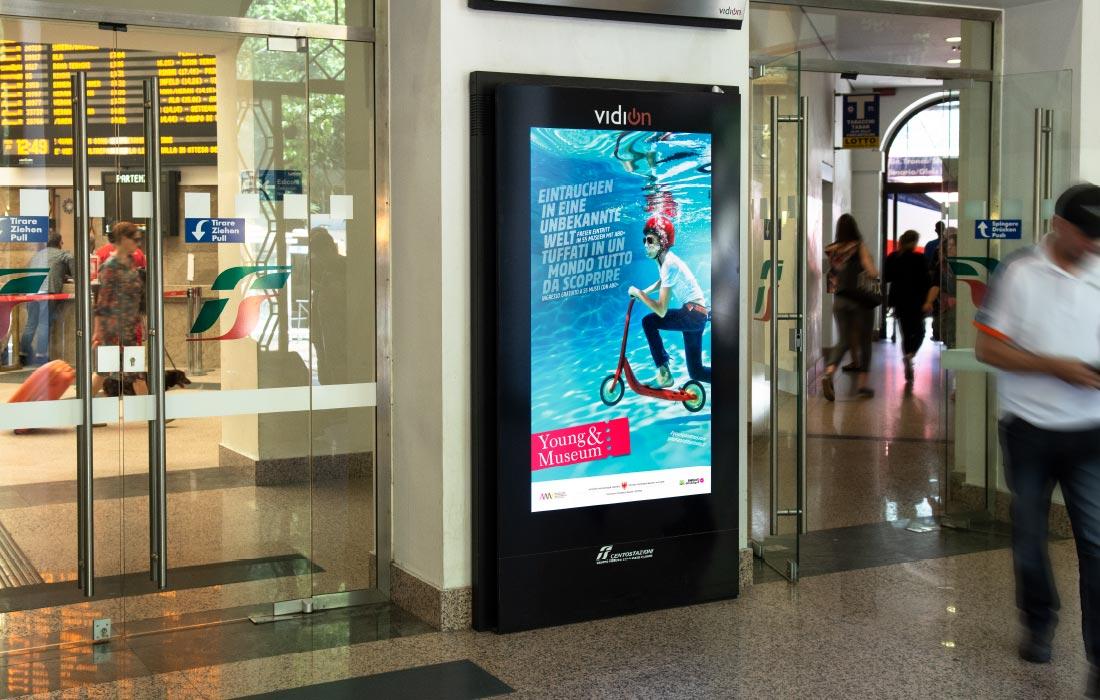 Digitales Plakat am Screen Vidion Digimupi der Centostazioni am Bahnhof Bozen. Young & Museum Kampagne mit einer Grafik von Waldemar Kerschbaumer, Grafikbüro adpassion Südtirol.