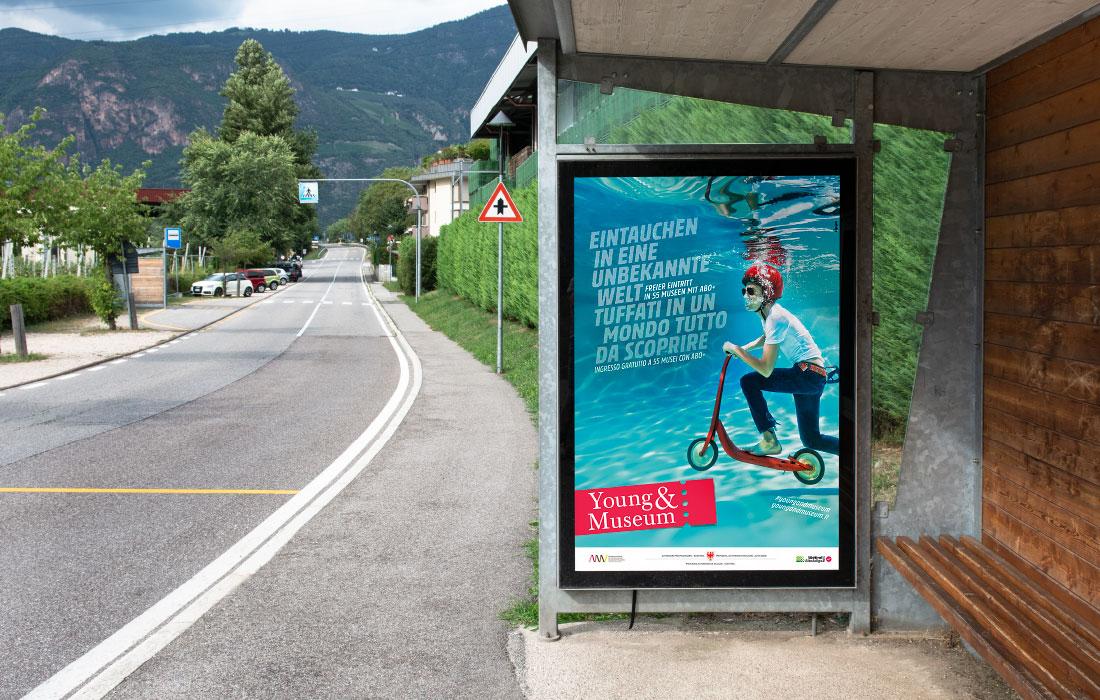 Young & Museum Citylight Plakat an den Bushaltestellen in Südtirol. Werbung für Kinder und Jugendliche des Amtes für Museen. Grafik von adpassion, Waldemar Kerschbaumer